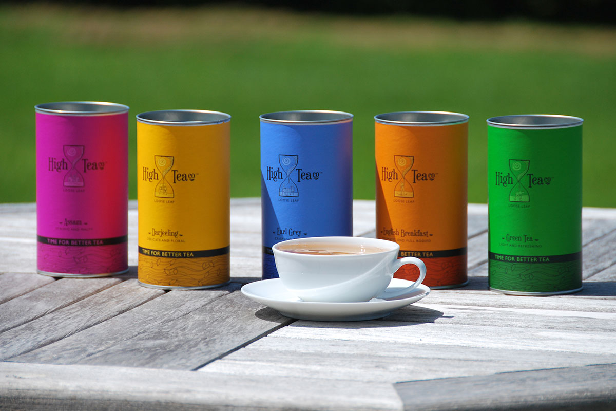 5 High Tea Co Flavours in their brightly coloured packaging (including pink, yellow, blue, orange & green) all placed on a table with a freshly brewed cup of tea in a white mug in the forefront.