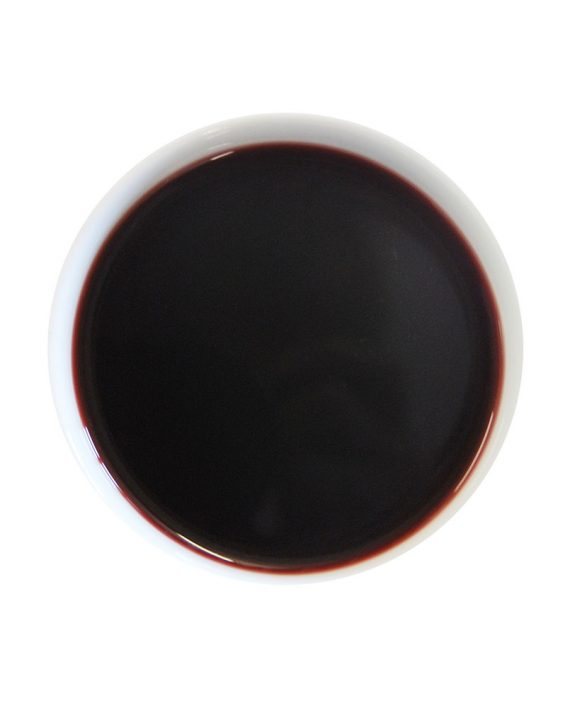Red fruit tea brewed in a white tea cup, the colour is a very dark red.
